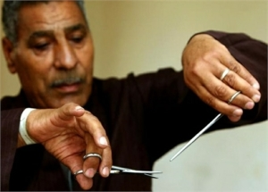 Hassan Hafez, a barber, mimics the way he used to perform female genital mutilation (FGM) in Minia June 13, 2006. Barbers in Egypt are people who perform circumcisions, although because of efforts of organizations like UNICEF, Hafez no longer circumcises women, only men. The practice of FGM dates back over two thousand years in Egypt and is widely practiced in all levels of society for Muslims and Christians alike. Many organizations have funded programs to help educate people about the risks and dangers of FGM in order to change people's opinions on this procedure which is seen by many as a necessary social norm. Picture taken June 13, 2006.  REUTERS/Tara Todras-Whitehill (EGYPT)